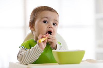 Cute baby eating healthy food with a spoon
