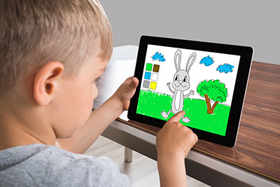 Boy logins in digital tablet screen while playing games