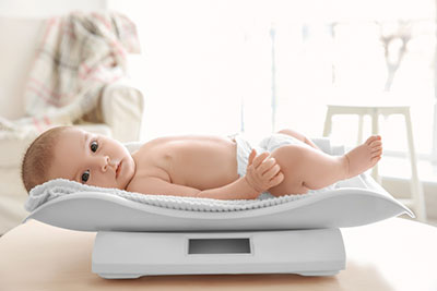 A baby lying on a baby scale