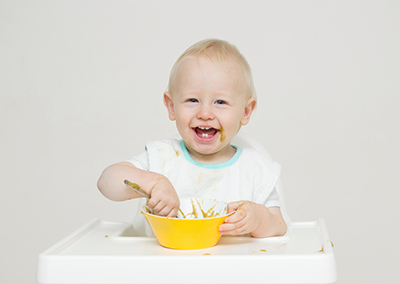 Baby in a white high chair with yellow bowl