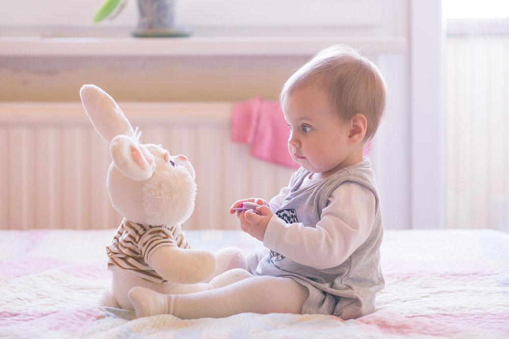 ten-month-old baby girl interact with plush toys