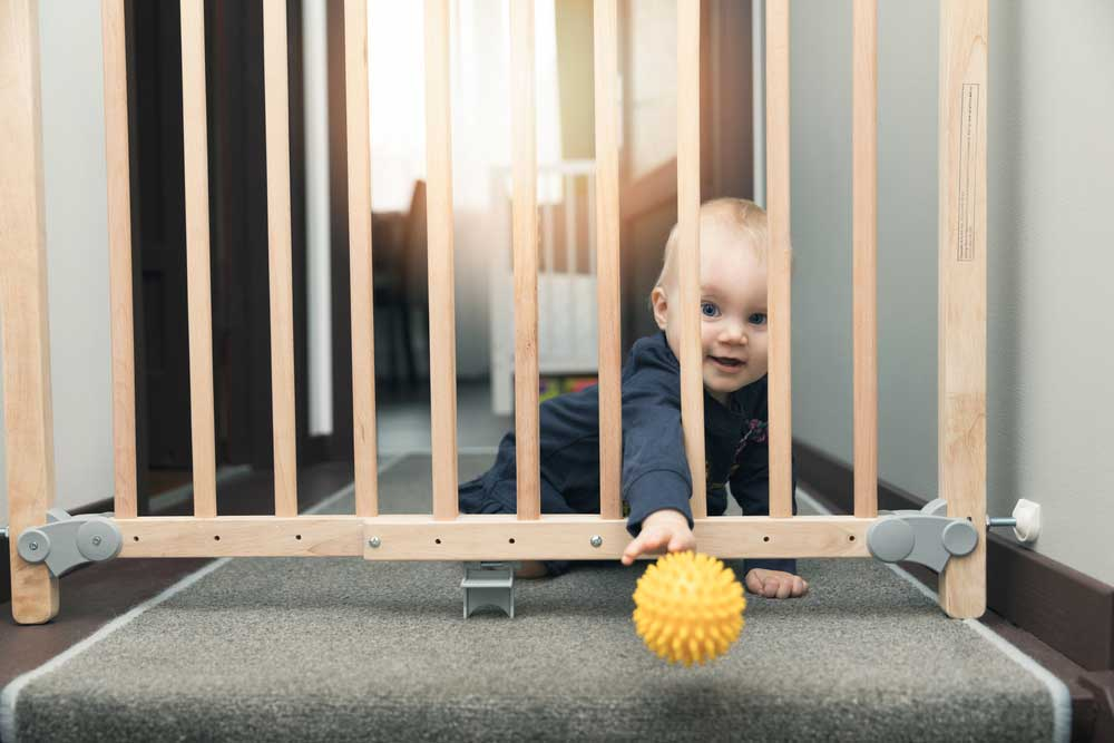 Child playing behind a safety gate