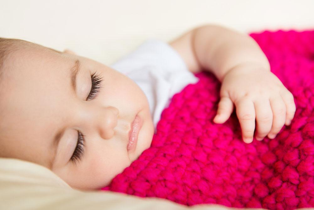 Cute Baby Sleeping in Knitted Blanket