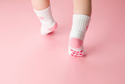 A baby resting in a crib while wearing baby socks