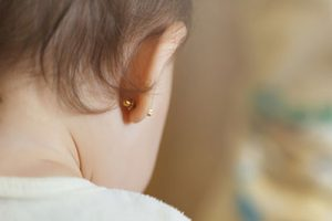 The cute baby wears ear studs