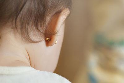 The cute baby wears ear studs