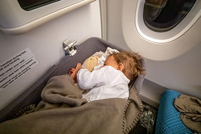 a baby sleeping on a bassinet in an airplane