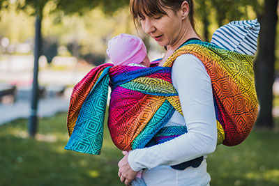 A mom carrying twins in a baby wrap
