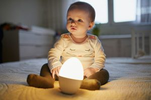 The happy child sat on the bed with the night light