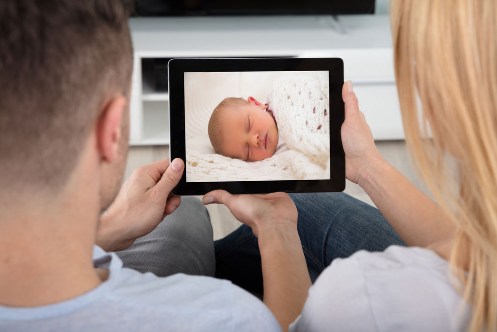Close-up Of Young Couple Looking At Baby Monitor On Digital Tablet At Home
