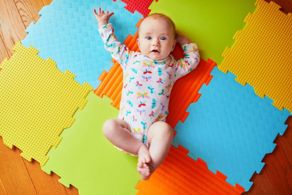 a baby lying on a foam floor mat