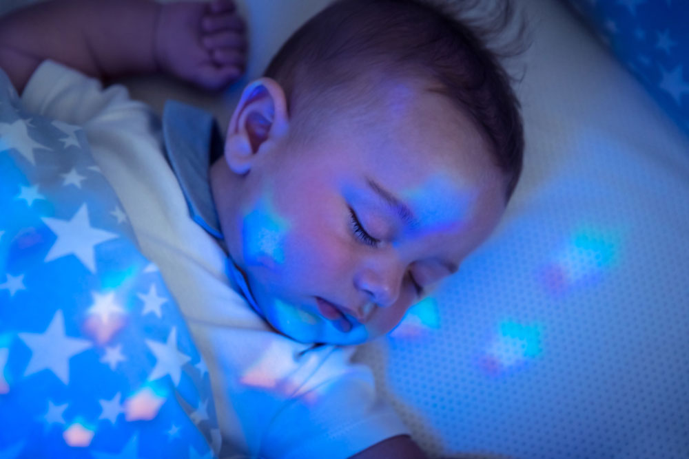 A cute baby boy sleeping under a star-lit night light