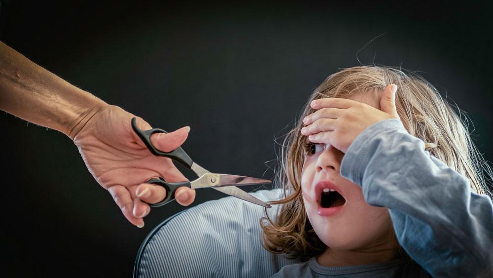 Little girl is very afraid of scissors