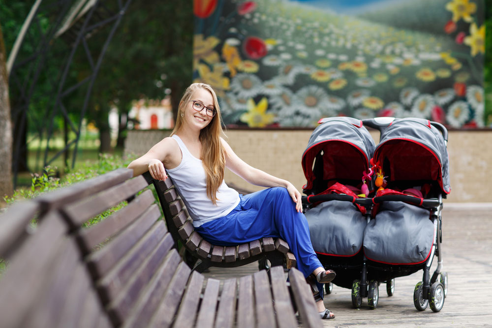 Woman Sitting Next To Double Stroller